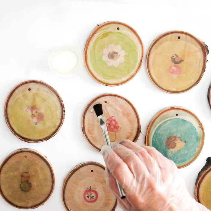 Using a paintbrush to add drops of resin to the wood slices.