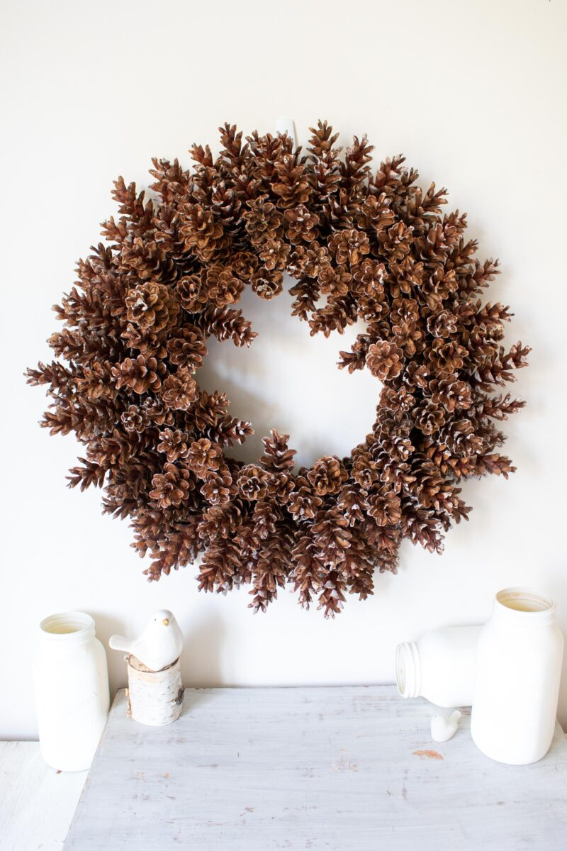 completed pineone wreath hung on a wall with white accessories