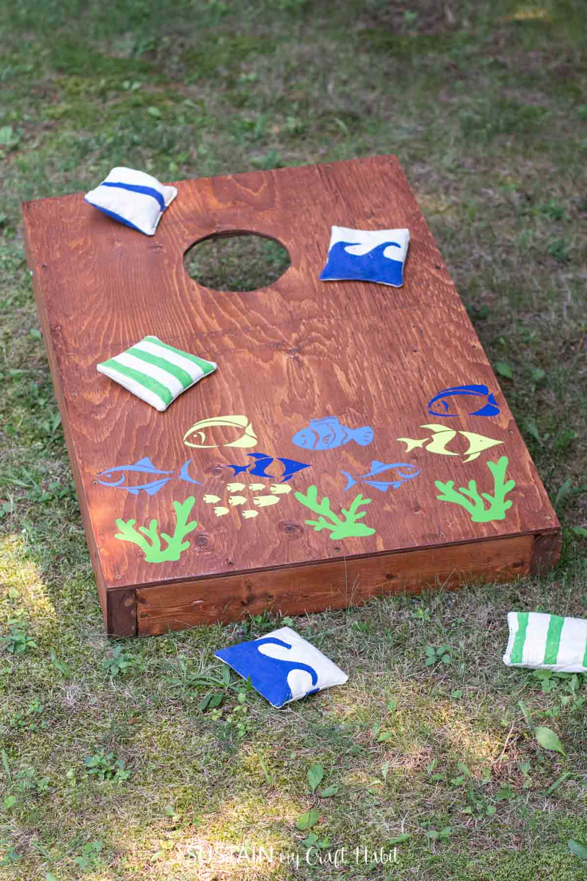 Cornhole board game embellished with fish decals using Cricut Joy and Smart Vinyl.