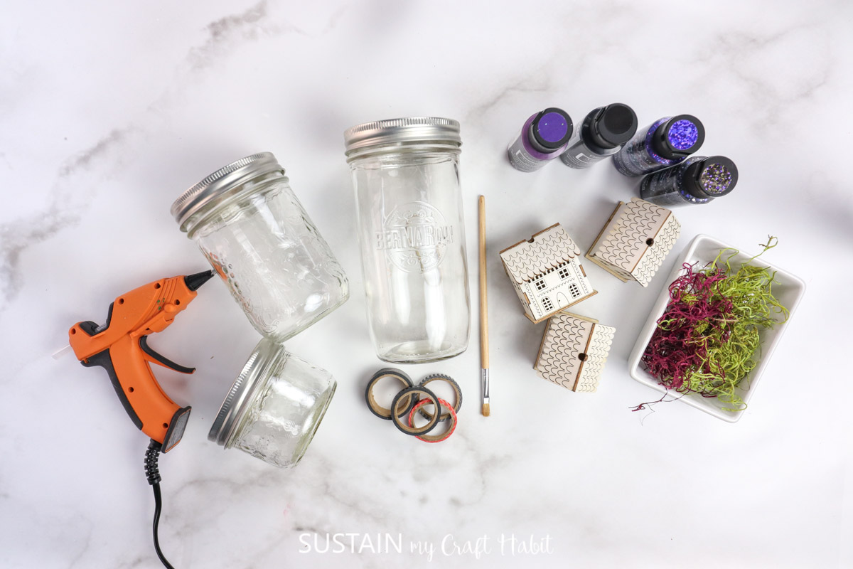 Materials needed to make a Halloween jar topper including mason jars, paint, wood houses, moss and hot glue.
