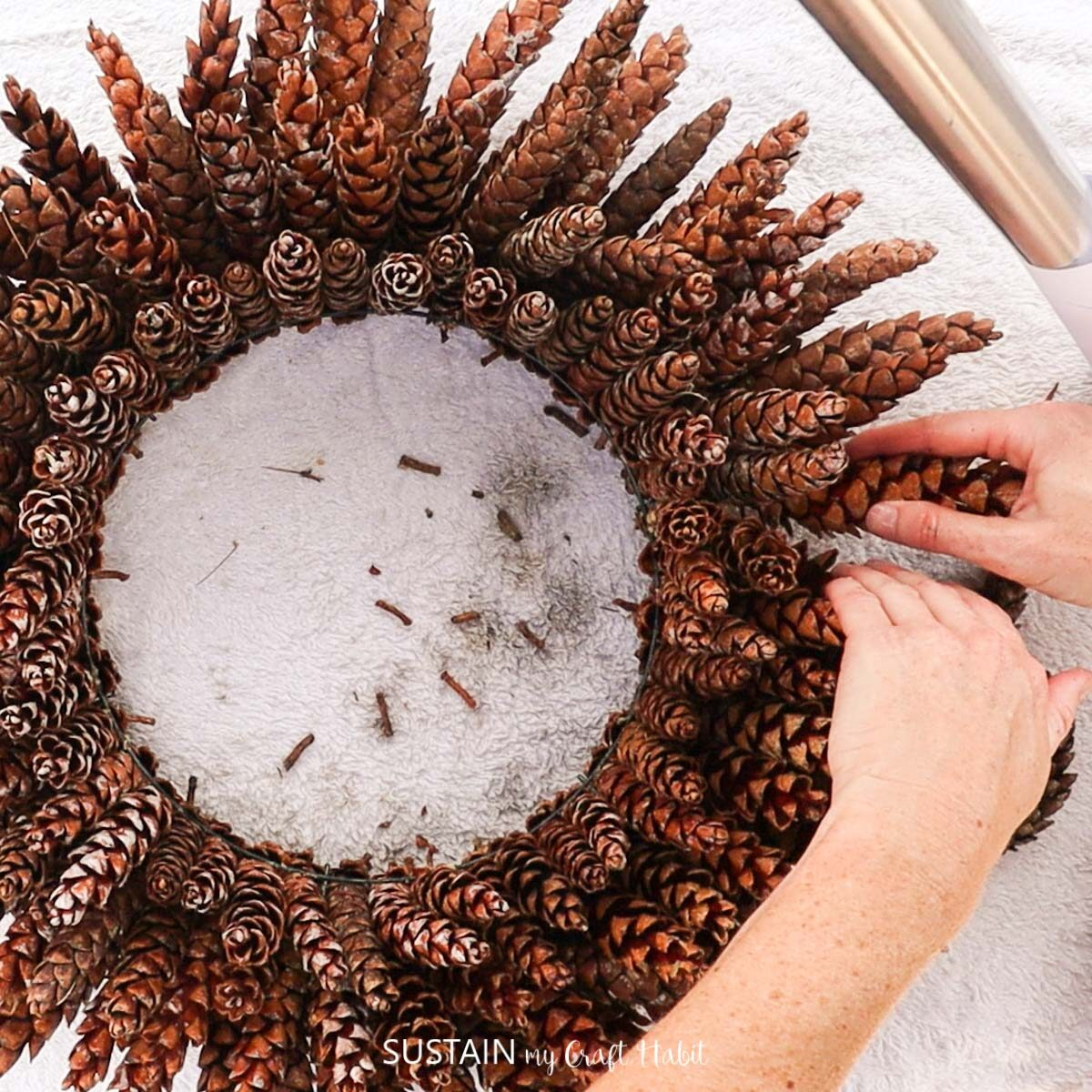 Adding the last pinecone to the wreath.