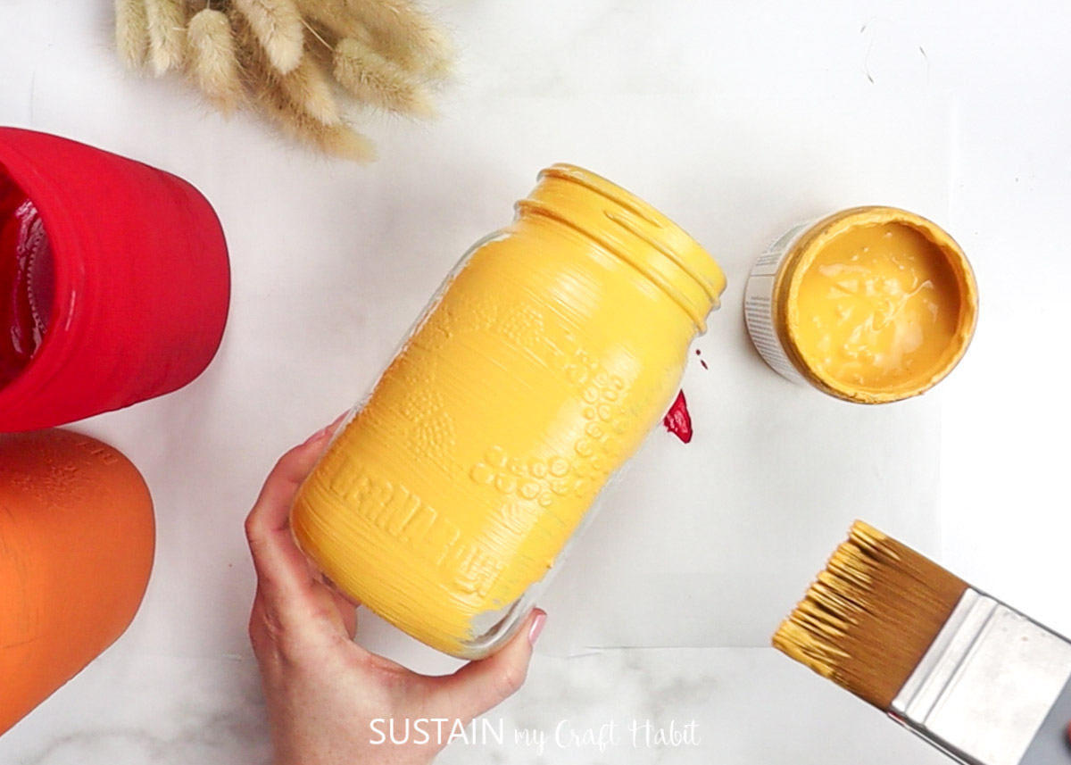 Painting a mason jar with yellow paint.