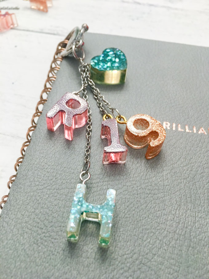 Monogram charms with resin attached to a notebook.