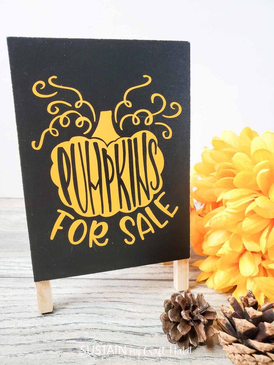 Dollar store pumpkin art craft with lettered vinyl on a mini black chalkboard.