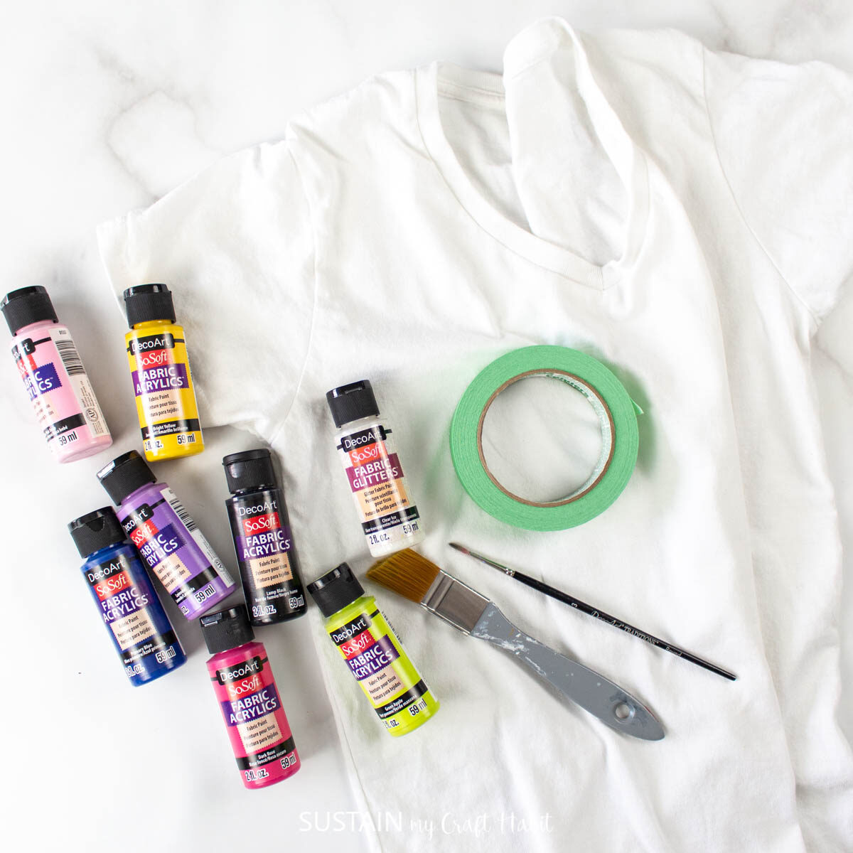 Materials needed for a tshirt painting including a shirt, paint, paint brush and masking tape.