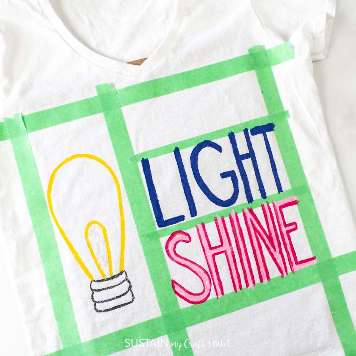 """Painting the word """"light"""" on the tshirt."""