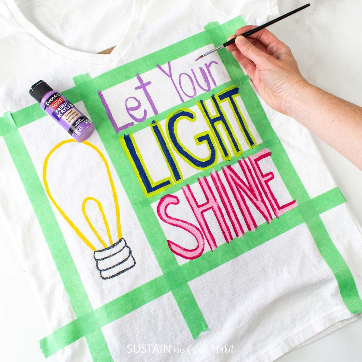 """Painting the words """"let your"""" on the tshirt."""
