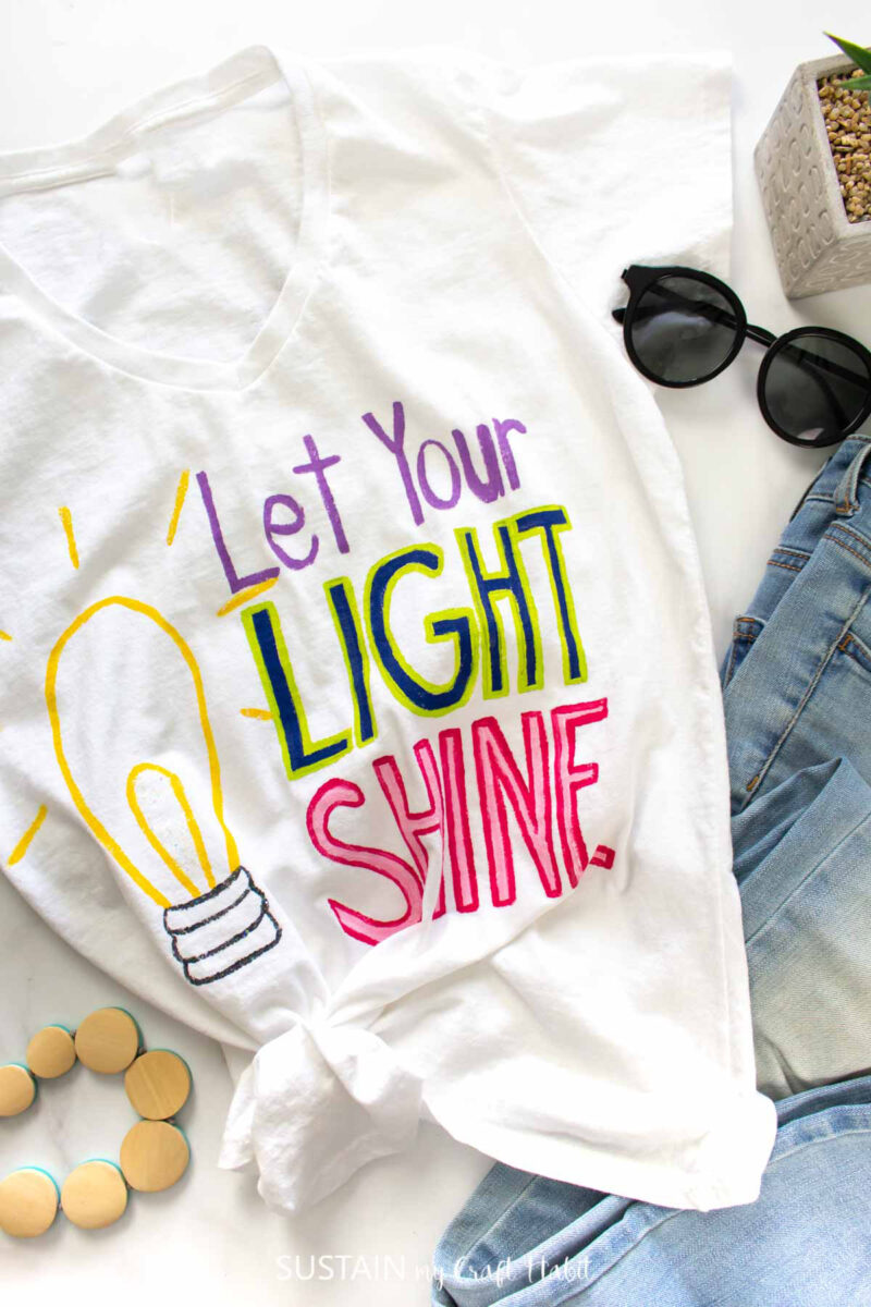 """Tshirt painting with """"let your light shine"""" in bright letters with a light bulb next to jeans and accessories."""