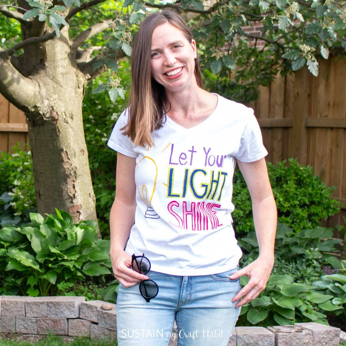 """Woman wearing the finished """"let your light shine"""" painted tshirt."""