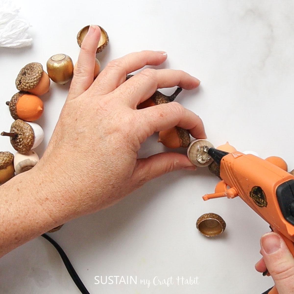 Adding hot glue to the acorns and acorn caps.