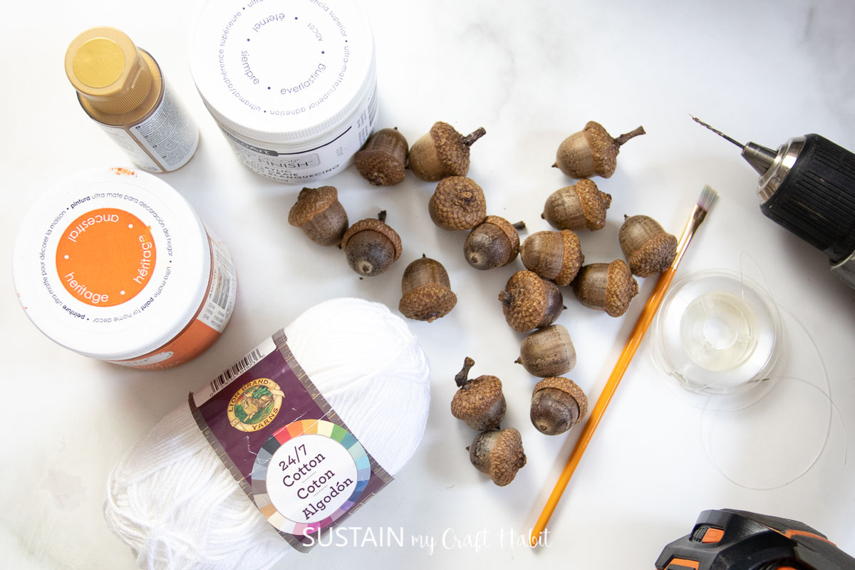 Materials needed to make an acorn garland, including acorns, paint, paint brush, drill, and string.