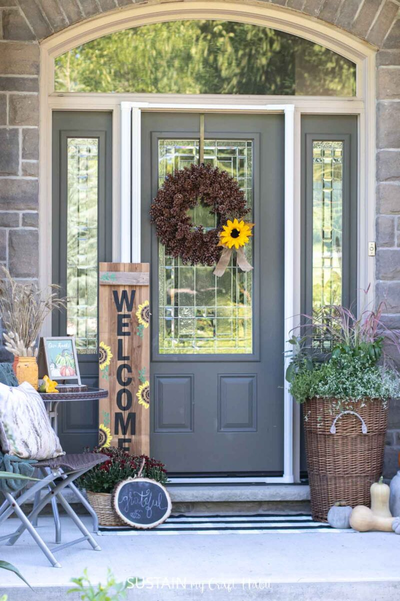 Porch decorated for fall with wooden signs, planter, wreath and accessories.