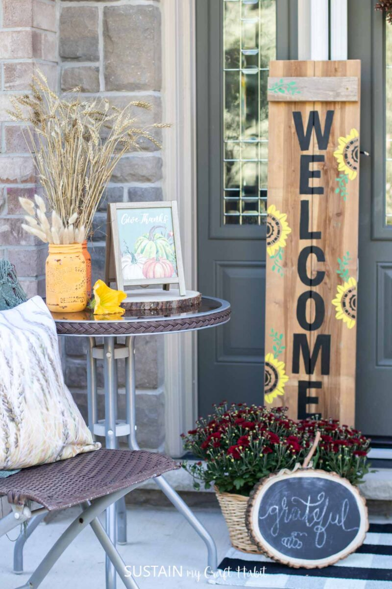 Wooden welcome sign next to a table and chairs with fall accessories.