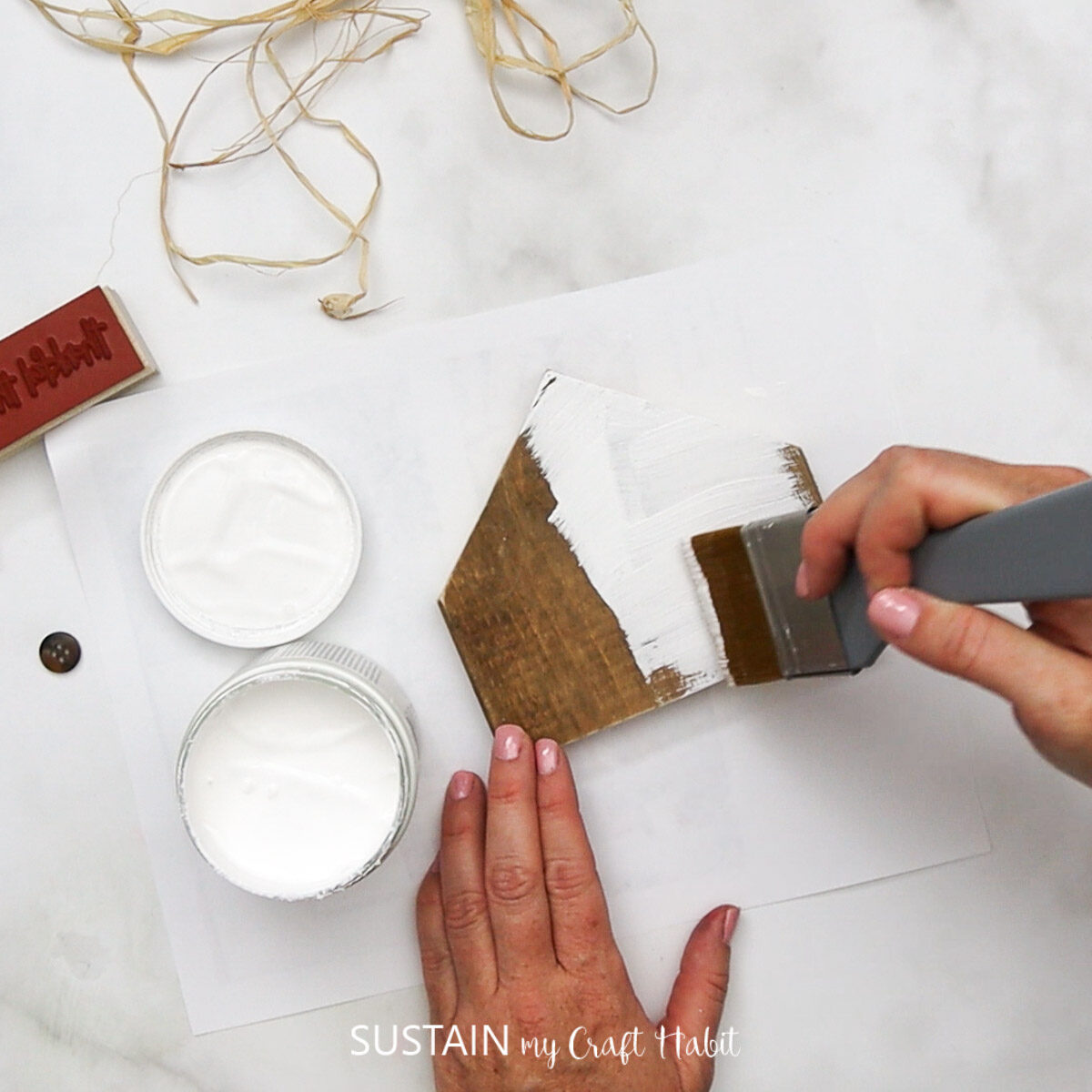 Painting scrap wood with white paint.