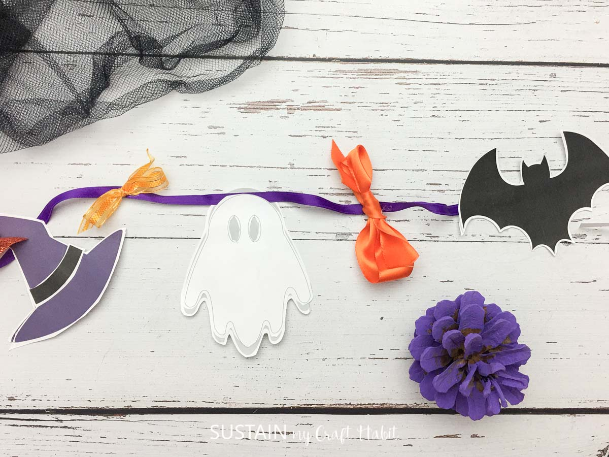 Halloween paper garland attached with purple ribbon.