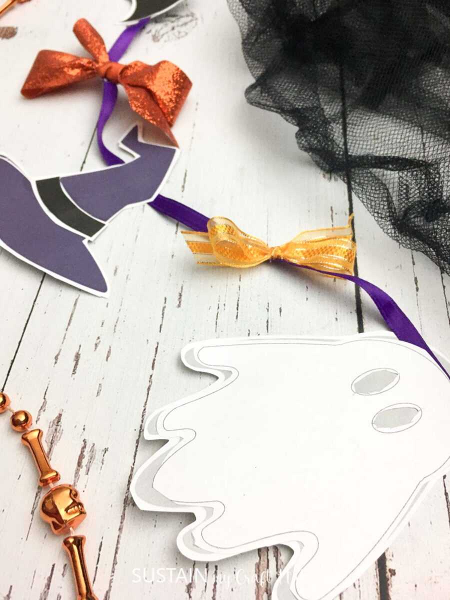 Halloween paper garland with characters attached with ribbon.