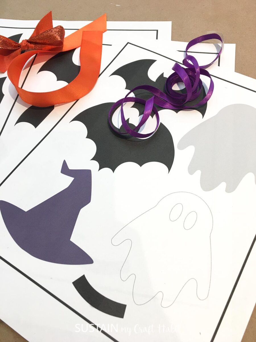 Materials needed for Halloween paper garland including a Halloween printable, ribbon and glue.