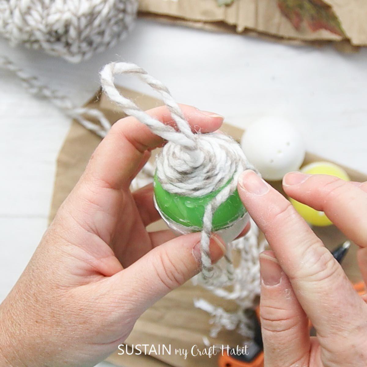 Gluing yarn around the plastic egg.