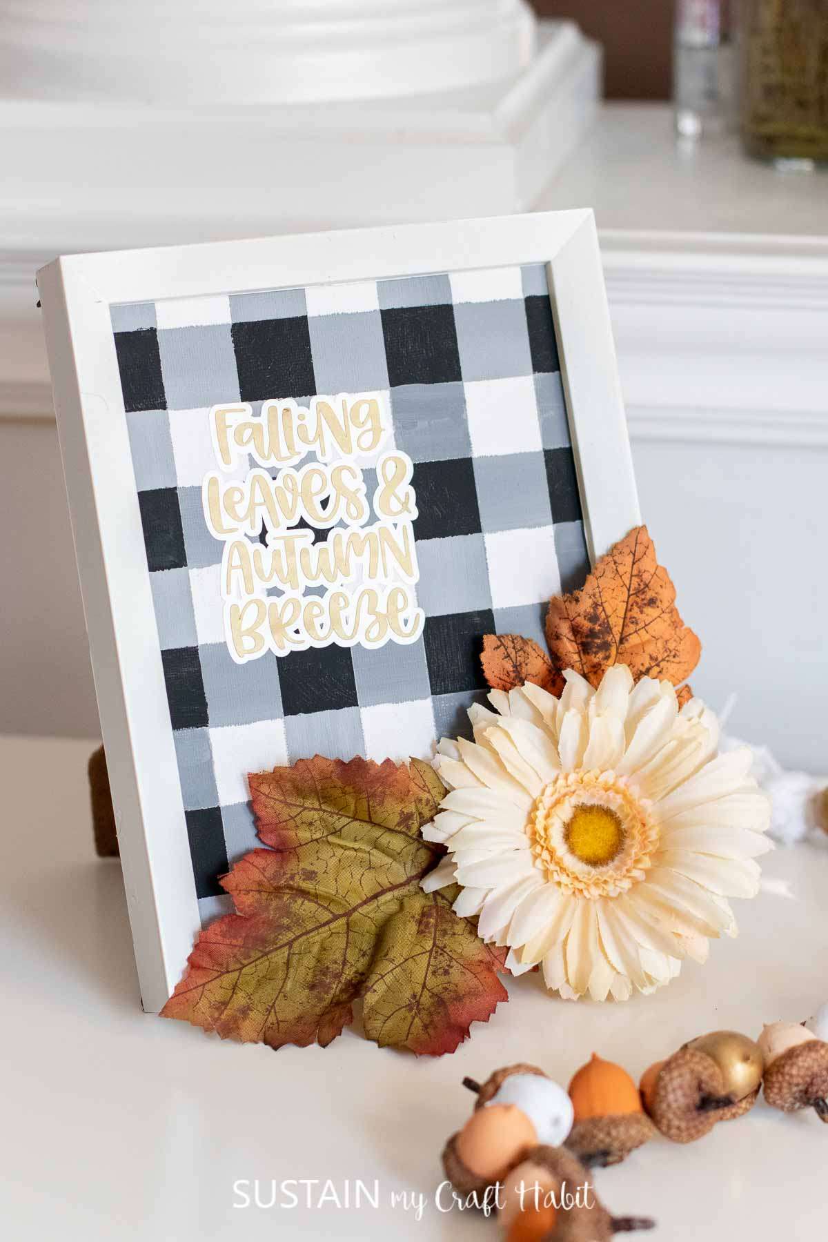"""Painted buffalo plaid pattern in a frame with a """"falling leaves and autumn breeze"""" cut out phrase and faux flowers and leaves."""