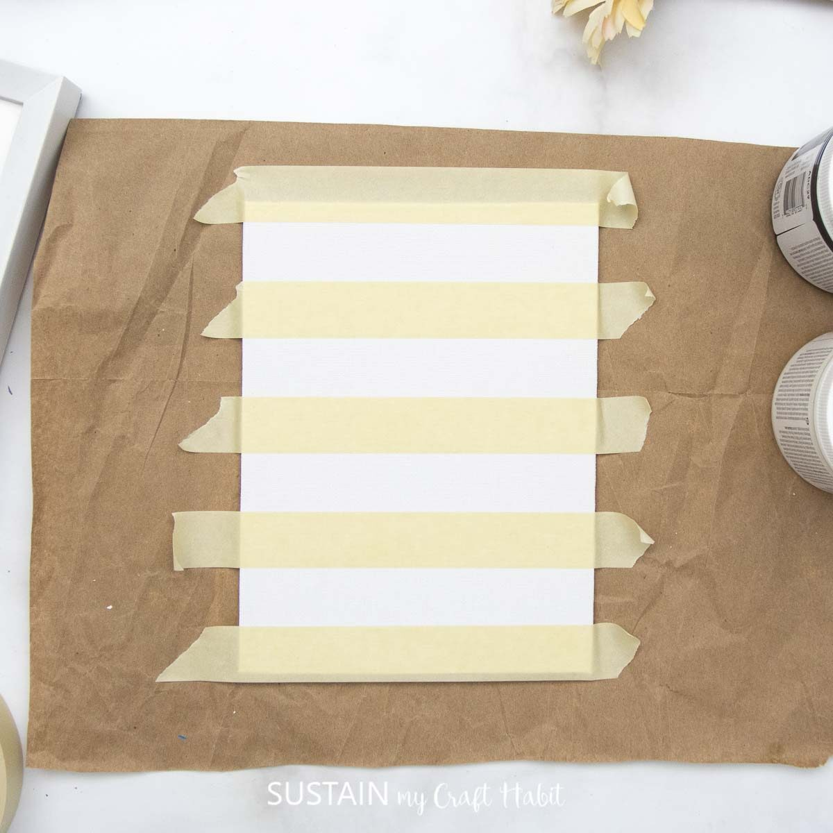 Adding painters tape horizontally on a piece of paper.