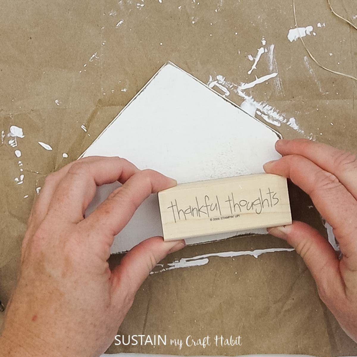 """Applying a """"thankful thoughts"""" rubber stamp to the painted scrap wood."""