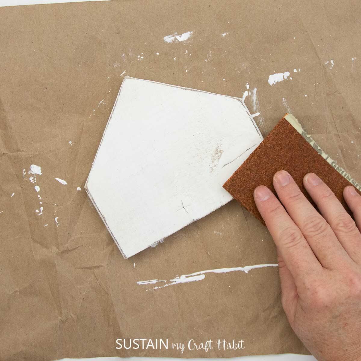 Sanding the painted scrap wood.