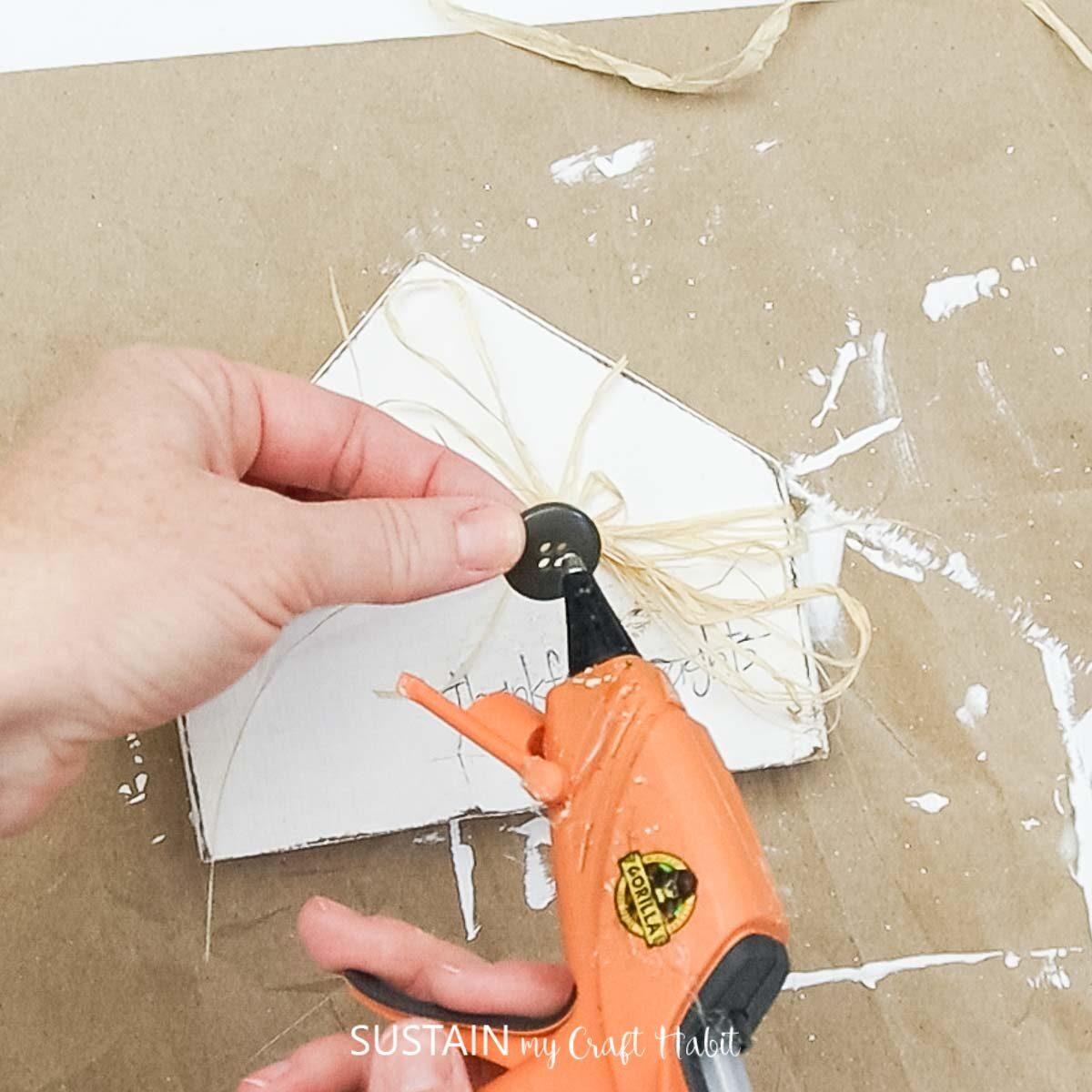 Adding hot glue to a button.